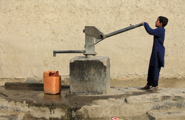 A boy draws drinking water from a well using a hand pump in Peshawar, Pakistan, on 4 March 2016. Photo: Fayaz Aziz / REUTERS