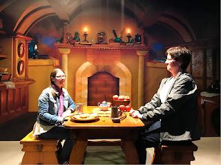 2 damen som sitter ved et bord foran en peis, en liten og en stor.