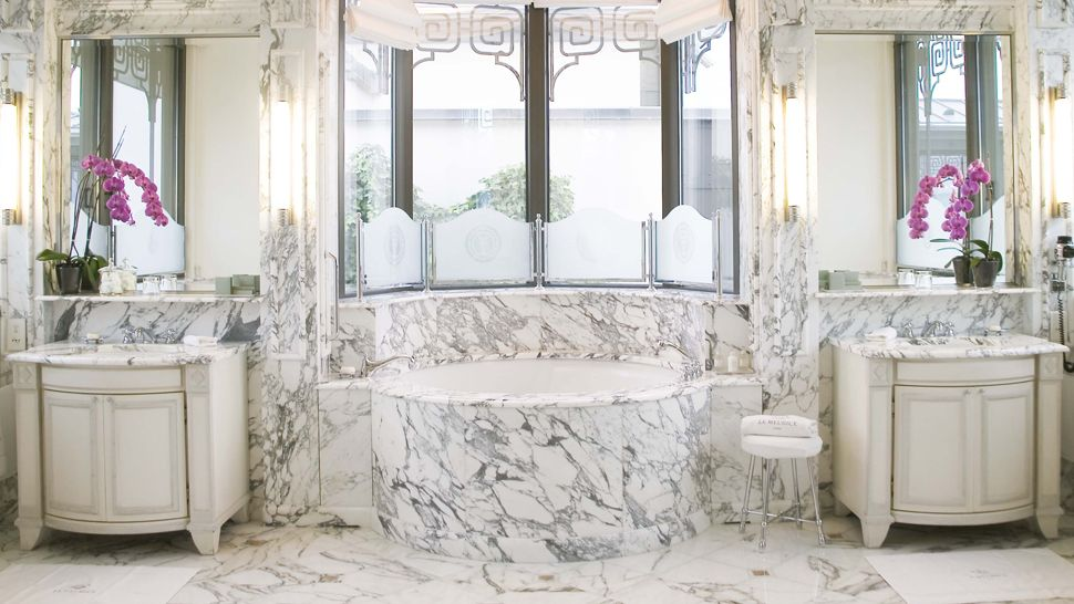 This is a gorgeous white marble pedestal sink with white marble floors