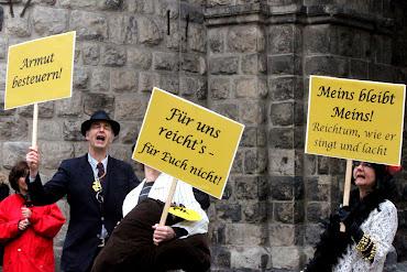 Kabarettistisch zugespitzte Transparente »der Reichen«: »Armut besteuern!«, »Für uns reicht's – für Euch nicht!«, »Meins bleibt Meins! Reichtum wie er singt und lacht«.