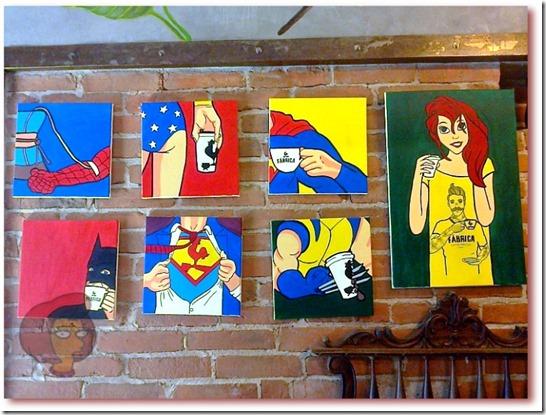 Foto de gravuras na parede com desenho de super heróis de quadrinhos (banda desenhada) que gostam de café: Homem-Aranha tomando uma transfusão de um café no Chemex, Mulher Maravilha com um copo de café take-away, Super Homem e Batman bebendo uma xícara de café, Wolverine transpassando com suas garras um copo take-away