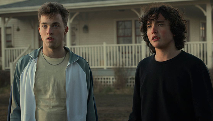 Jonathan Kent, vestindo blusa amarela, casaco esportivo e corrente no pescoço, e Jordan Kent, vestindo blusa preta de manga comprida. Ambos olham para frente e ao fundo a casa da família.