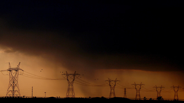 Rain falls behind power lines near Adelanto at the end of a scorching hot day, 31 August 2017. Photo: Luis Sinco / Los Angeles Times