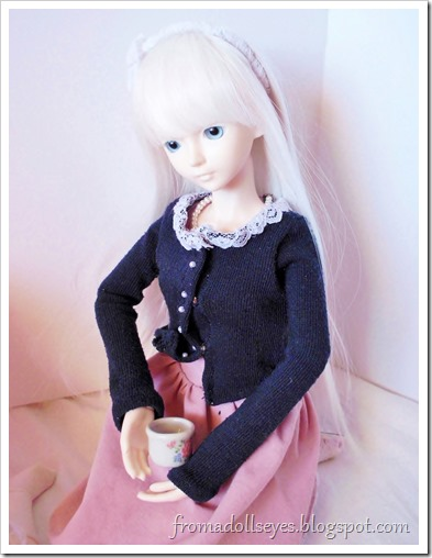 A ball jointed doll having tea.