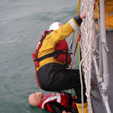 17 July 2011 – Crew Member Scott Rowland getting ready on the scramble net to bring the casualty into the Jason's Cradle off Poole's all-weather lifeboat. Photo: RNLI Poole/Anne Millman