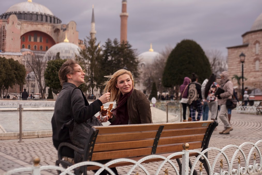 eating simit in front of hagia sophia