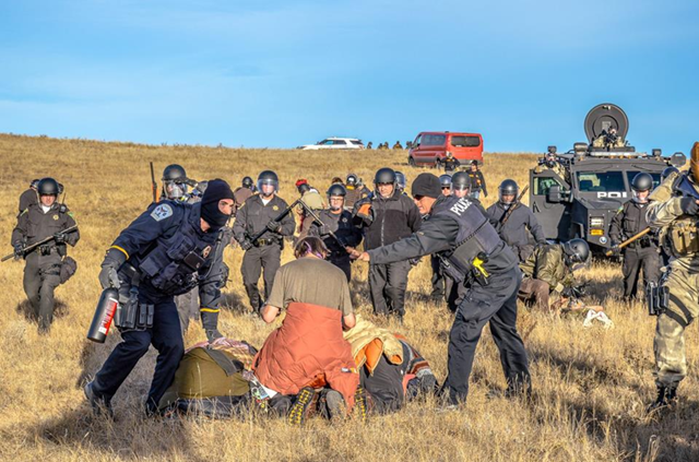 Police attack peaceful demonstrators at the Dakota Access Pipeline protest with batons and pepper spray, 22 October 2016. The Civil Liberties Defense Center noted reports of humiliation, beatings by police, and unnecessary strip-searches of arrestees: 'The actions of police against the land and water protectors at Standing Rock are depraved, abusive, and disgraceful. They are exceedingly disrespectful and radically humiliating to the people who have occupied this land since time immemorial. Photo: Walter Ruiz