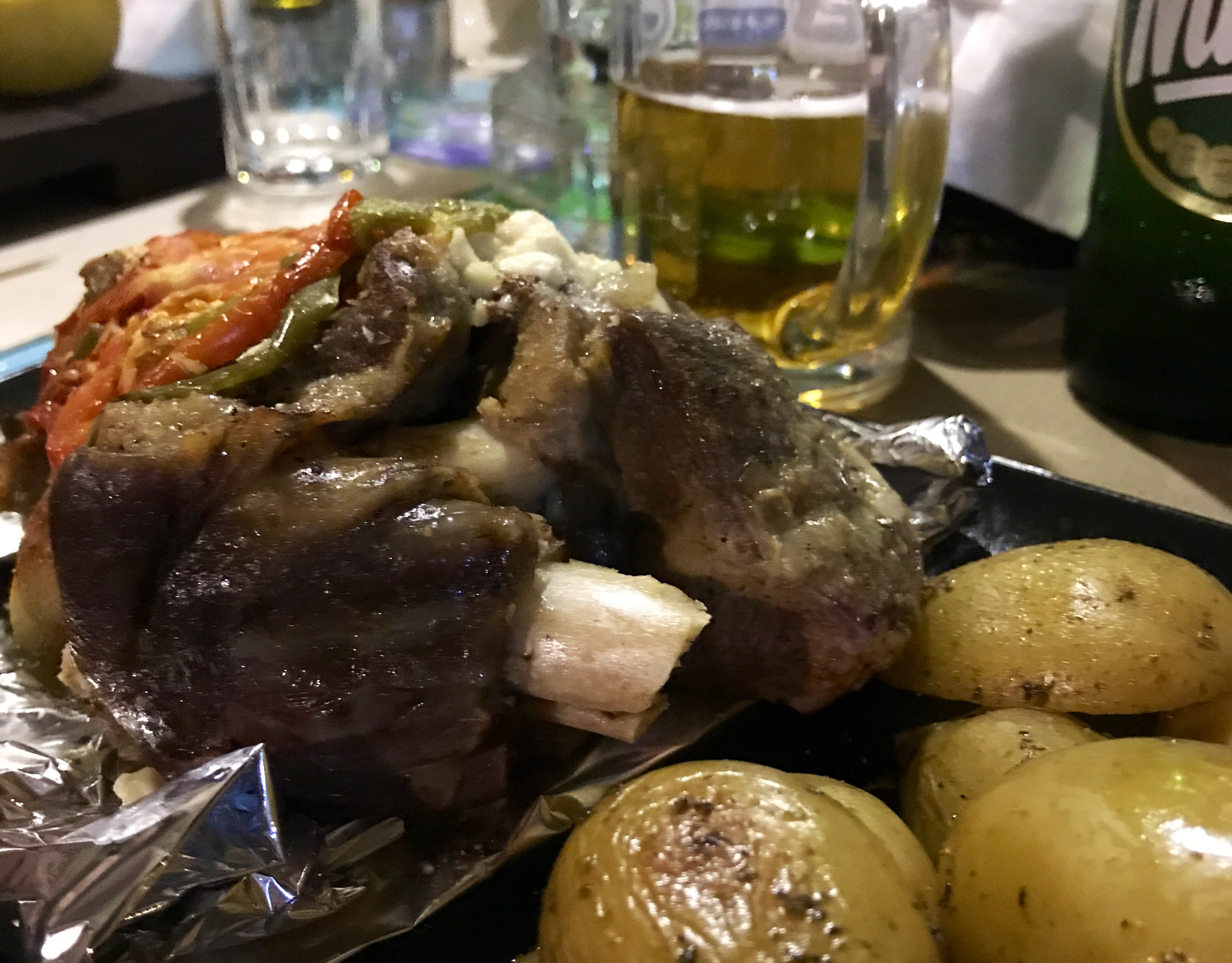 Et stort kjøttstykke på sølvpapir. I forgrunnen småpoteter og et glass med øl i bakgrunnen