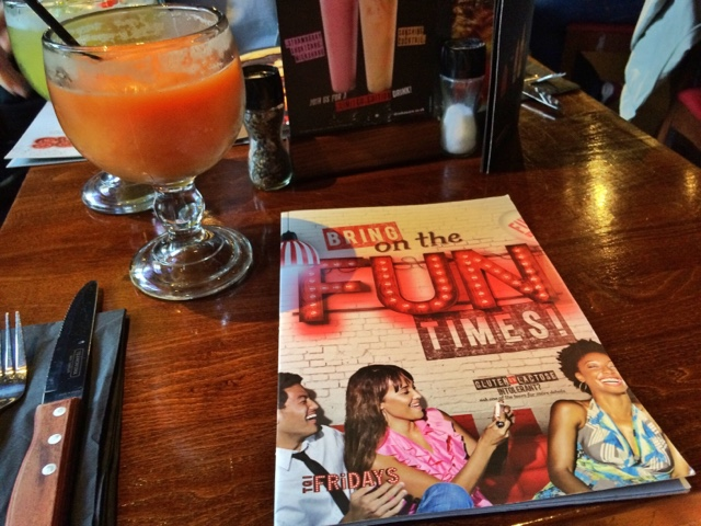 a TGI Fridays menu on the table, a large orange cocktail sits next to it with cutlery.