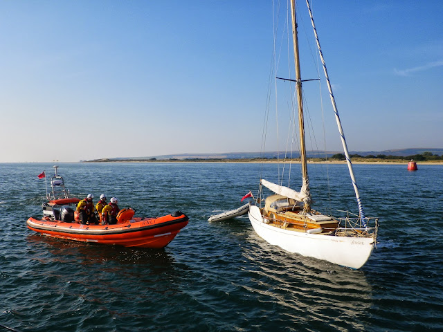 Poole ILB coming alongside the yacht after towing it off Hook Sands with the ALB. A crew member is below decks checking for any ingress of water. Photo: RNLI/Poole