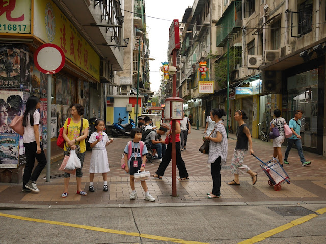 people waiting at a bus stop in Macau's Three Lamps District