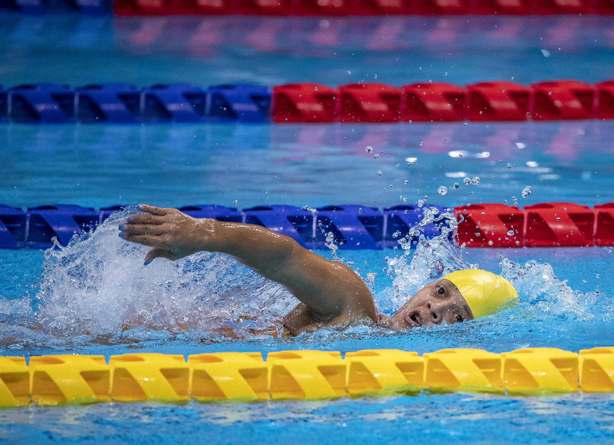 Joana Maria da Silva nada sem óculos e de touca amarela. A atleta está com a cabeça e um braço acima da água.