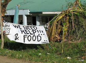 A makeshift sign outside a house reads 'We need help & food'