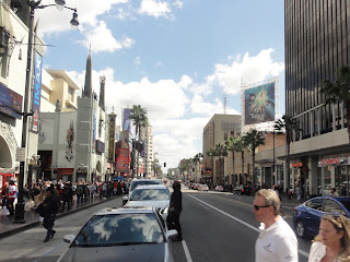 Trafikkert gate med bygninger og mange mennesker på begge sider.