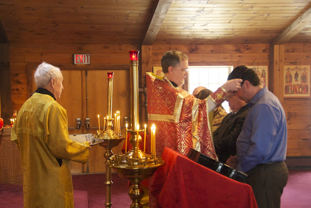 Fr. John places the crosses on the catechumen.