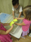 Children using sponges in water.