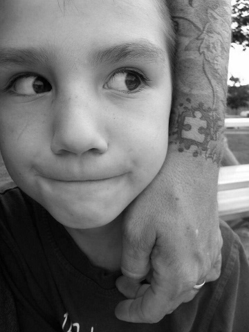 boy with arm around him that has a tattoo of a puzzle piece