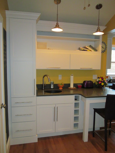 Bar sink, flip-up cabinet doors for easy access.