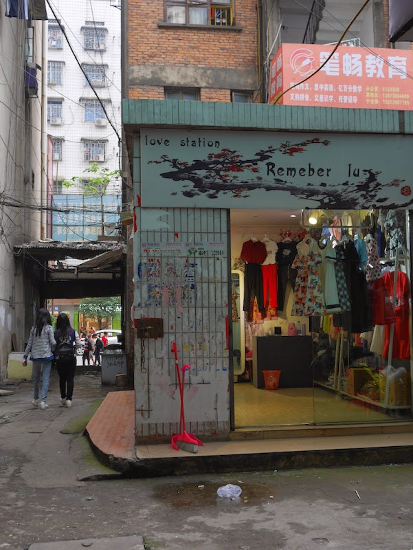 "storefront sign with words ""love station Remeber lu"" for a young women's clothing store in Shaoyang, Hunan"