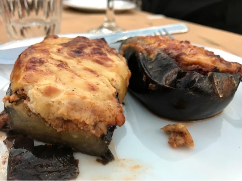 To halve auberginer på en tallerken. Den ene er skåret over og avslører kvernet lammekjøtt under ostesausen.