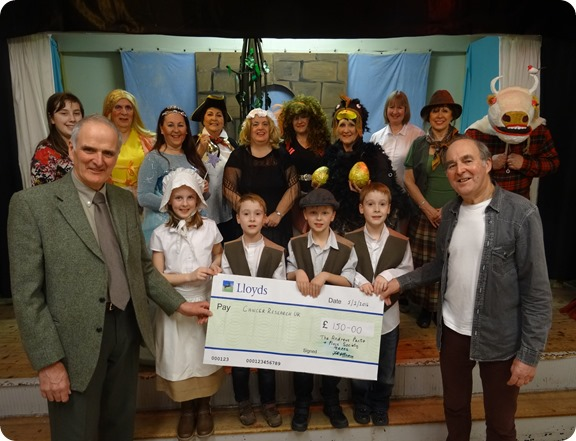 John Pass (left) receives the cheque from Fred Allman  (right) with the panto cast