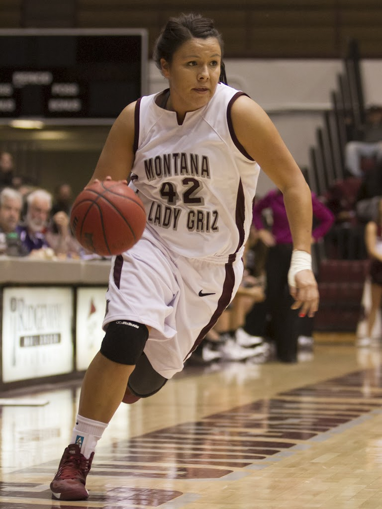 Shanae Gilham, a freshman forward from Bozeman, Mont., drives towards the rim without hesitation as the clock winds down on Montana's 2012-13 season opener.  Gilham's nine points and two rebounds helped the Lady Griz beat the Carroll College Knights 72-45.  Dahlberg Arena in Missoula, Mont., October 30th, 2012.