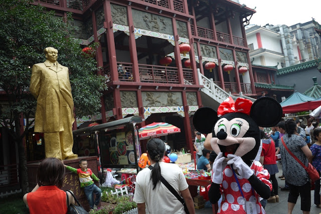 imitation Minnie Mouse near a golden colored statue of Mao Zedong in Changsha, China
