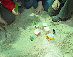 Children build a hill of sand and add model houses.