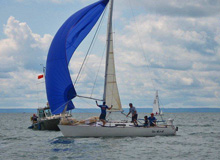 J/27 one-design sailboat- sailing across finish line