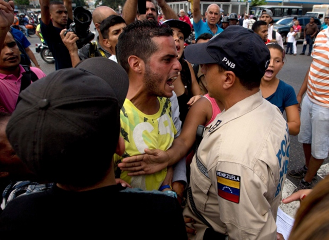 A man who was waiting in line at a grocery store argues with a Bolivarian National Police officer as people continue to wait for food, sold at regulated prices, to arrive to the store in Caracas. Photo: Fernando Llano / Associated Press