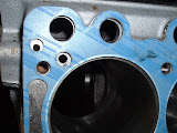 See the small hole top left, that is where oil gets from the block to head to oil the rockers. That is where the Felpro head gaskets leak.