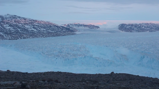 Screenshot of a video showing a massive iceberg calving event captured at Helheim Glacier in Greenland on 22 June 2018, at 11:30 pm. The event occurred over approximately 30 minutes. Photo: Denise Holland / New York University