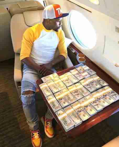 Floyd Mayweather poses with stacks of 100 dollar bills in his private jet