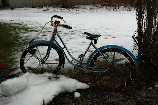 Old bicycle in the snow strunf with holiday lights