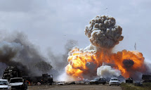 Vehicles belonging to forces loyal to Libyan leader Muammar Gaddafi explode after an air strike by coalition forces, along a road between Benghazi and Ajdabiyah March 20, 2011. It is a war that Barack Obama didn't want, David Cameron didn't need, Angela M
