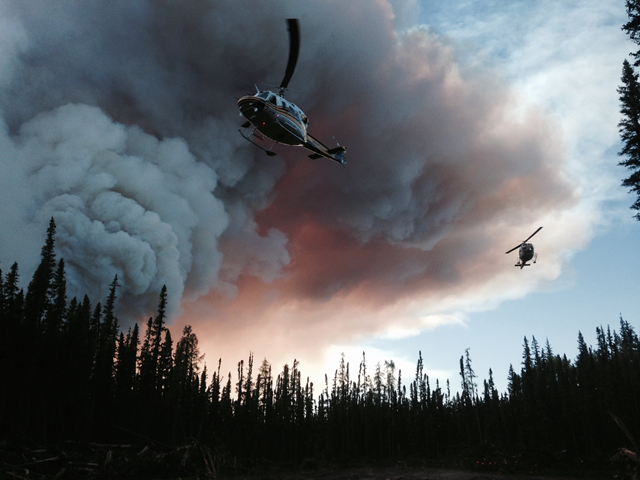 Two helicopters land beneath a column of smoke from a forest fire in British Columbia, 8 August 2017. Photo: BC Wildfire Service