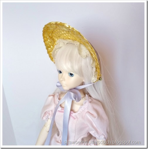 A white haired ball jointed doll wearing a straw half bonnet with a pale purple ribbon.