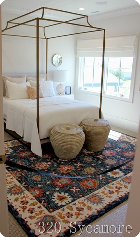 white bedding with colorful rug