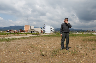 Kimiko's father stands near to where his house once stood