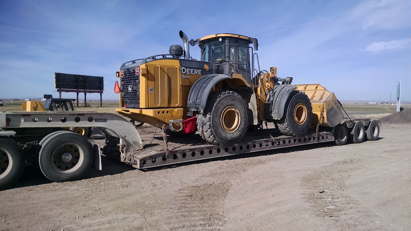 John Deere 824 loader chained onto a flatbed trailer