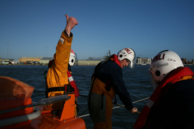 Crew member signalling to the coxswain that all is okay with the tow
