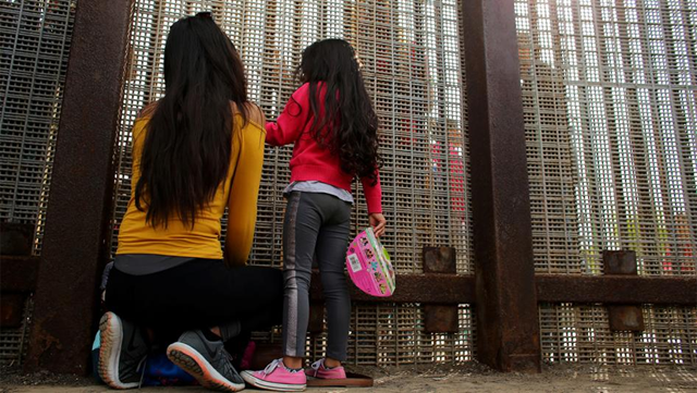 Families chat while separated on either side of the US-Mexico border fence at Border Field State Park, California, 19 November 2016. Photo: Mike Blake / Reuters