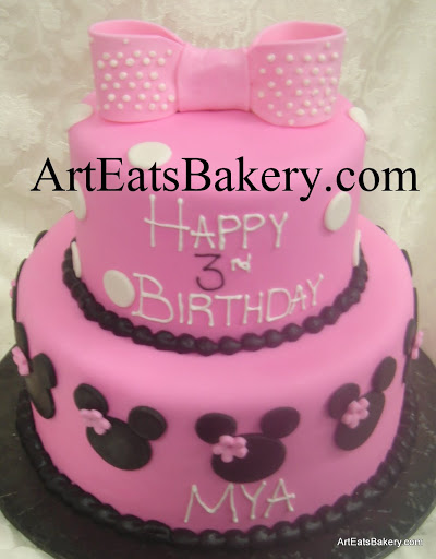 Two tier pink fondant creative unique girl's birthday cake design idea with black Minnie Mouse heads, polka dots, flowers and edible bow topper