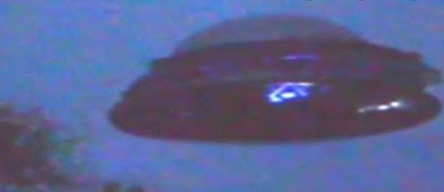 Close up zoom in of a real UFO with an Alien seen through the window.