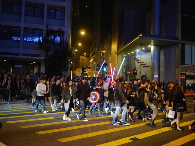 people carrying lightsabers and a Captain America shield across an intersection in Hong Kong