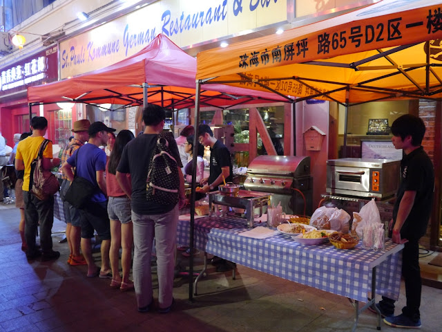 tent selling food and drink outside of the St. Pauli Kommune German Restaurant & Bar in Zhuhai, China.