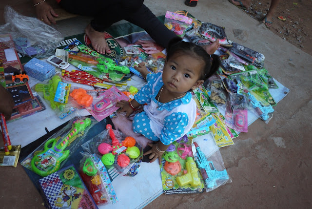 little girl sitting amongst toys for sale at a small shop