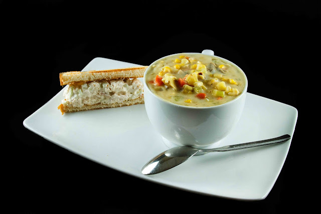 corn chowder in a large white soup mug next to half a sandwich on a white platter