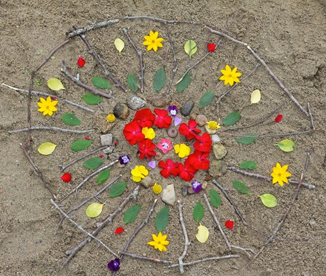 Completed-Beach-Mandala-Made-with-Sticks-Stones-and-Flowers