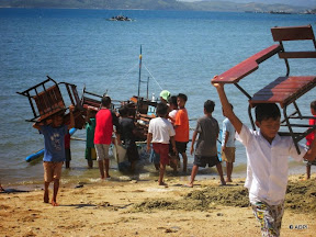 People unloading chairs from a small boat on a beach